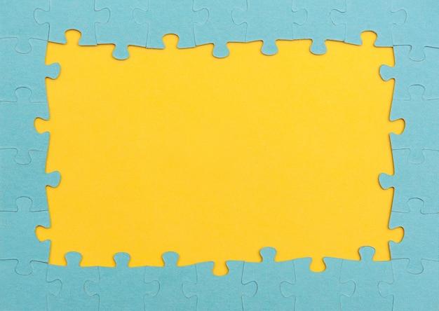 Ramka wykonana z niebieskich puzzli na żółtym tle