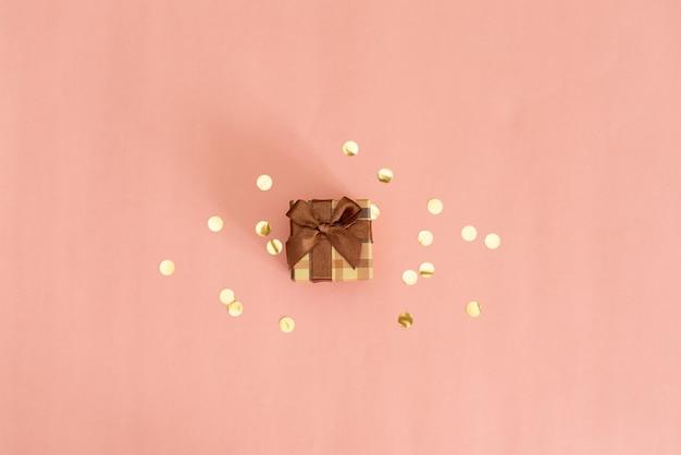 Ramka z bombką, prezentem, wstążką, kosmetykiem i dekoracjami w pastelowym różowym kolorze