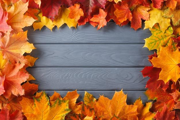 Ramka z kolorowych liści jesienią na teksturowanym drewnie