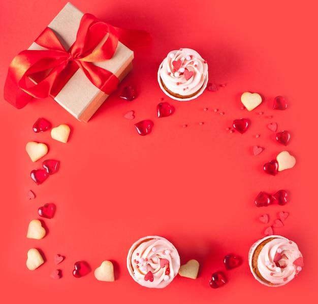 Ramka z kremowym kremem babeczki ozdobiona cukierkami w kształcie serca, makaronikami, pudełkiem prezentowym. koncepcja walentynki. widok z góry. skopiuj miejsce.