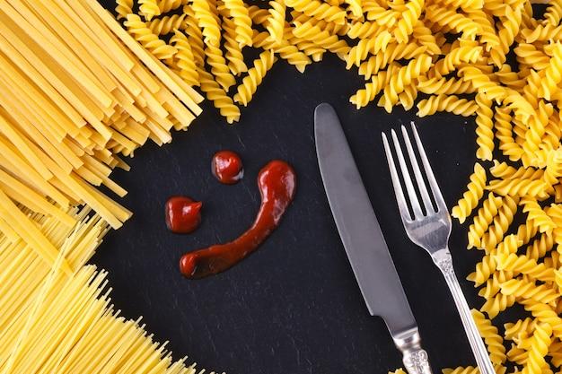 Ramka z niegotowanej paasta na łupku z keczupem