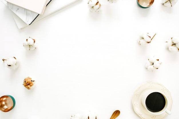 Ramka z patyczków kosmetycznych, filiżanka kawy, złote talerze, notes na białej powierzchni