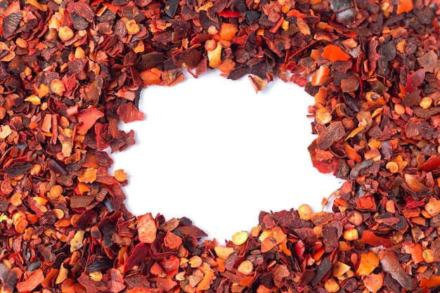 Ramka z pokruszonej czerwonej papryczki chili, suszonych płatków pieprzu cayenne na białym tle z miejscem na kopię