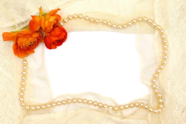 Ramka z pomarańczowych kwiatów, pereł i białej koronki