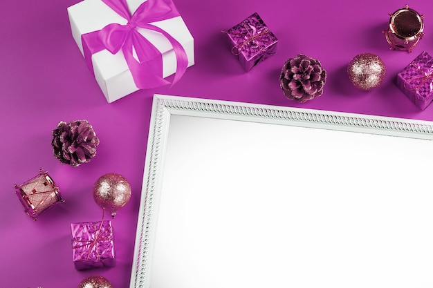 Ramka z pustą białą przestrzenią z dekoracjami świątecznymi i prezentami na różowej ścianie. pocztówka wesołych świąt i szczęśliwego nowego roku z wolnym miejscem na teksty powitalne.