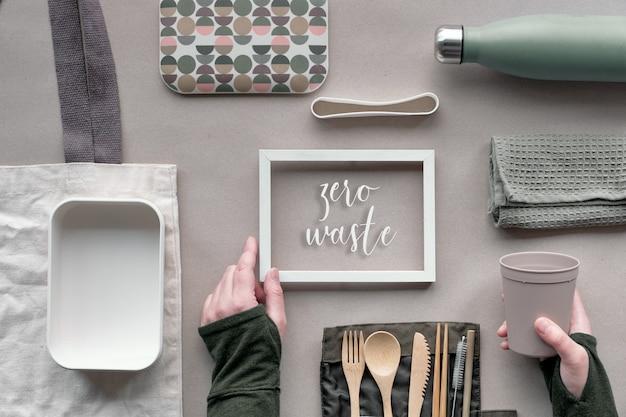 """Ramka z tekstem """"zero odpadów"""", widok z góry, zielona koncepcja zestawu obiadowego. płaski, ekologiczny zestaw na wynos na lunch - bambusowe sztućce, pudełko na lunch, bawełniana torba i ręka z filiżanką kawy na papierze rzemieślniczym."""