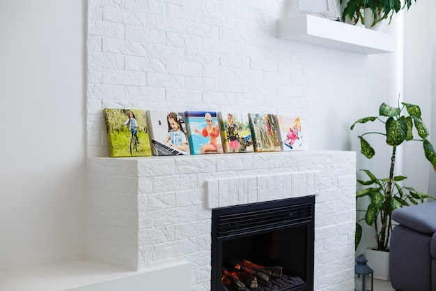 Ramki kolażu z kwiatowymi plakatami na teksturowanej ścianie z cegieł, nad nowoczesną kanapą, makieta wystroju wnętrza