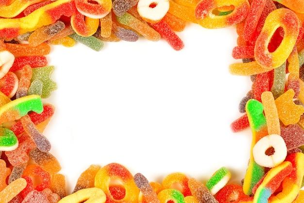 Ramki różne żelki cukierki na białym tle. widok z góry. miejsce na tekst lub projekt.