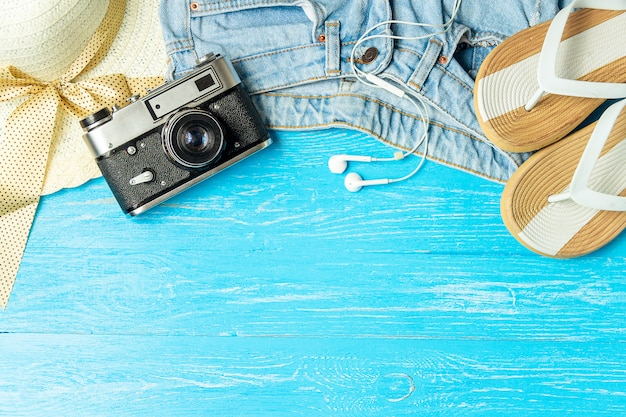 Ramowa elegancka żeńska słomianego kapeluszu kapci cajgów kamera na błękitnym drewnianym tle, copyspace dla teksta, wakacje.