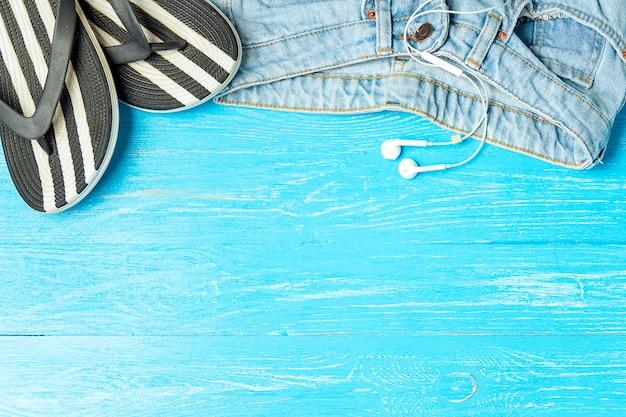 Ramowe eleganckie kapcie dżinsy słuchawki na niebieskim tle drewnianych, miejsce, letnie wakacje.