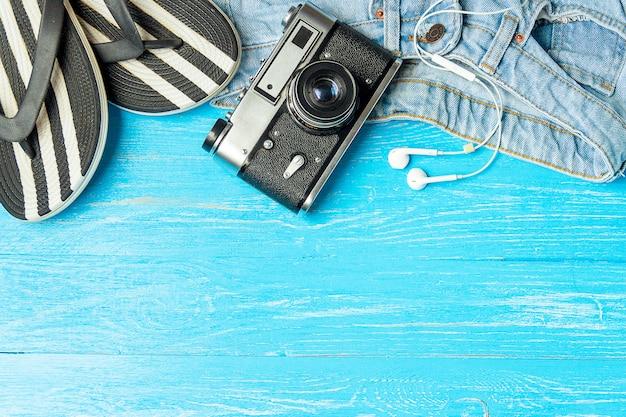 Ramowe eleganckie żeńskie kapcie cajgów kamery słuchawki na błękitnym drewnianym tle, copyspace, wakacje.