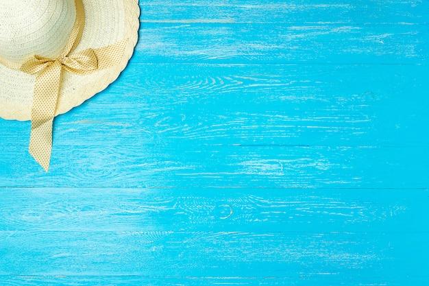 Ramowy elegancki żeński słomiany kapelusz na błękitnym drewnianym tle, copyspace dla teksta, wakacje.