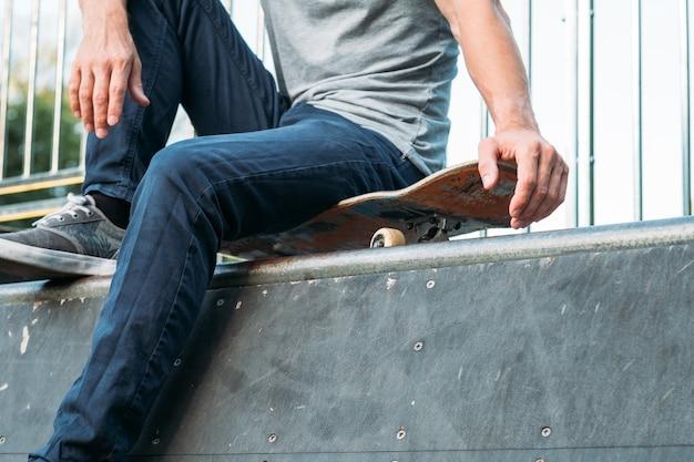 Rampa do skateparku. ekstremalny styl życia. wolność kultury młodzieżowej. mężczyzna siedzący na deskorolce.