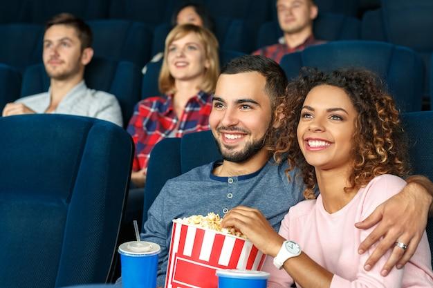 Randka w kinie! młoda szczęśliwa wielokulturowa para je popkorn i ogląda filmy w kinie wpólnie