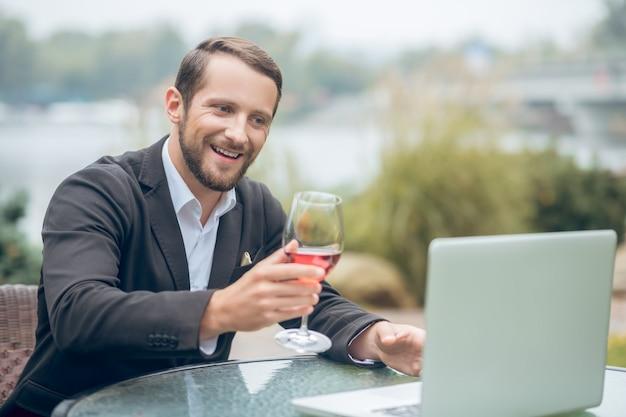 Randki w internecie. młody brodaty mężczyzna atrakcyjny przy lampce wina na czacie online na laptopie w letniej kawiarni na świeżym powietrzu