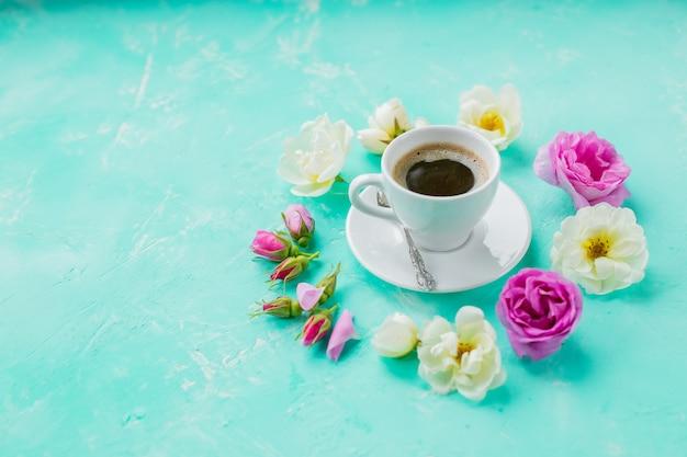 Ranek filiżanka kawy i piękne róże kwitną na lekkim tle, odgórny widok. przytulne śniadanie. mieszkanie świeckich styl. płaskie miejsce pracy w domu tło. miejsce na niebieskim tle. przytulne śniadanie