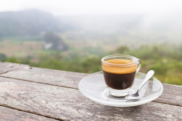 Ranek filiżanka kawy na drewnianym stole z górą przy wschodem słońca i morzem mgła, wizerunek z kopii przestrzenią.