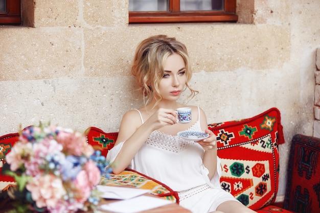 Ranek kobieta pije kawowego odpoczynkowego obsiadanie na tureckiej kanapie. kobieta marzy, piękna blond fryzura, gorąca herbata w filiżance w jej rękach