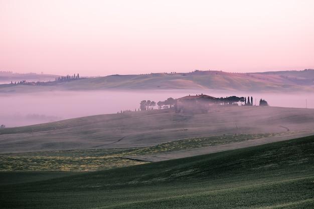 Ranek mgły widok na domu wiejskim w tuscany, włochy