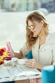 Ranek. uśmiechnięta dziewczyna z telefonem, filiżanką kawy i jogurtem