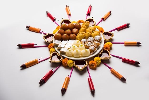 Rangoli lub projekt wykonany przy użyciu lampy naftowej lub lampy naftowej diya, kwiatów i słodyczy, takich jak gulab jamun, rasgulla, kaju katli, morichoor lub bundi laddu, gujiya lub karanji na obchody diwali