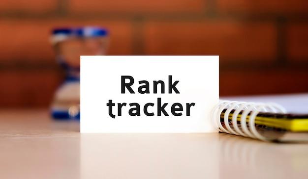 Rank tracker - tekst seo w białej kartce z notatnikiem i klepsydrą