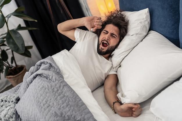 Rankiem. przyjemny, przystojny mężczyzna ziewa, próbując się obudzić