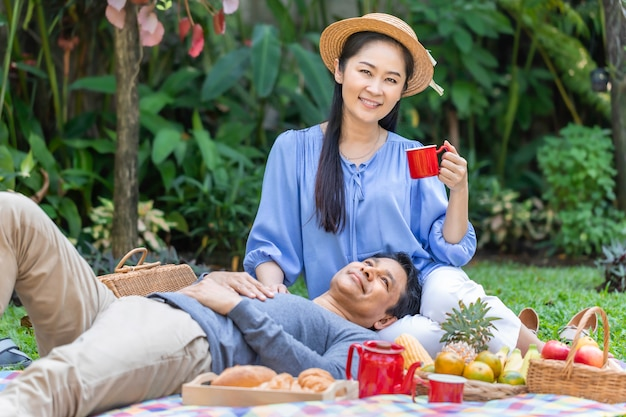 Rankiem. starsza azjatycka para pije kawę i pinkin przy parkiem.