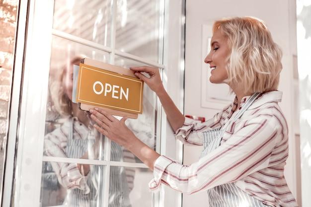 Rankiem. zachwycona atrakcyjna kobieta stojąca przy drzwiach i kładąca na nich otwarty napis