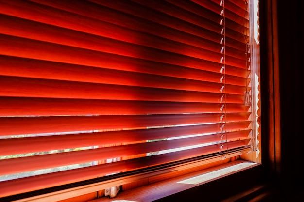 Rankiem zamknięte pomarańczowe plastikowe żaluzje ze światłem słonecznym. okno z żaluzjami. projekt wnętrz salonu z poziomymi oknami. zamknięta żaluzja. cień i światło