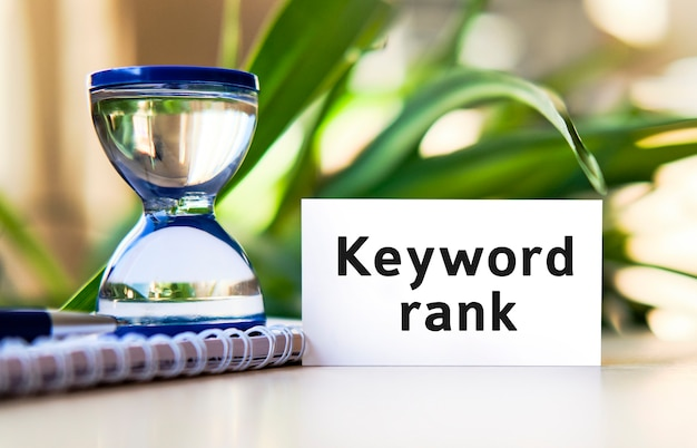 Ranking słów kluczowych - tekst koncepcji biznesowej na białym zeszycie i zegarze klepsydrowym, zielone liście kwiatów