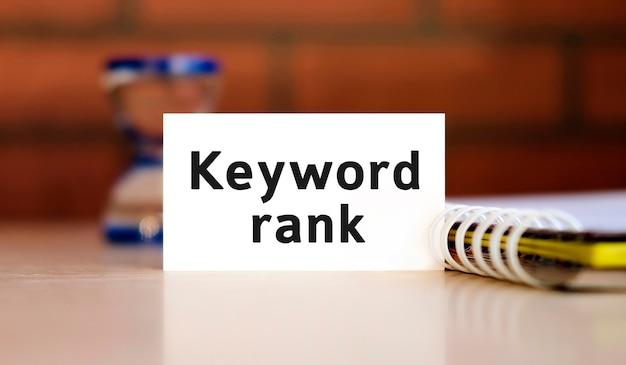 Ranking słów kluczowych — tekst na białej kartce z notatnikiem i klepsydrą