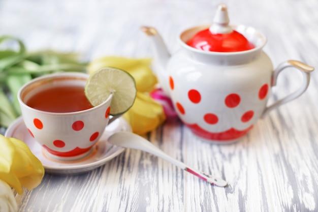 Ranku śniadanie herbata w filiżance kolorowi grochy z ciastkami