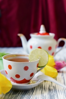 Ranku śniadanie herbata w filiżance kolorowi grochy z różowymi kwiatami
