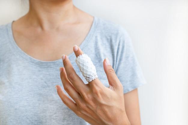 Ranny bolesny palec z białym bandażem z gazy