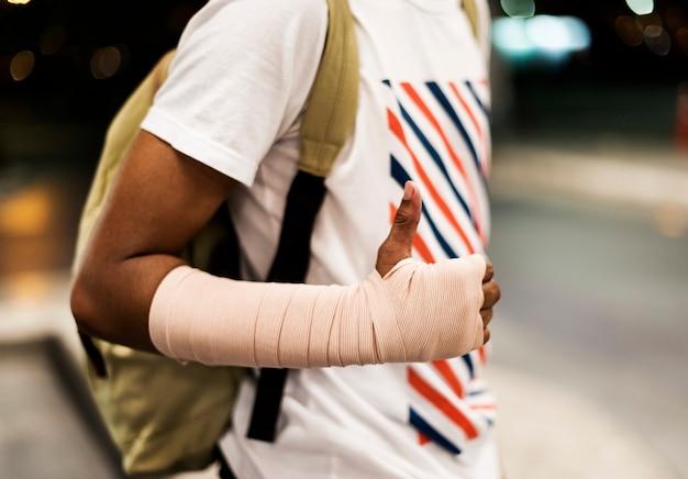 Ranny młody człowiek z poparciem ręki