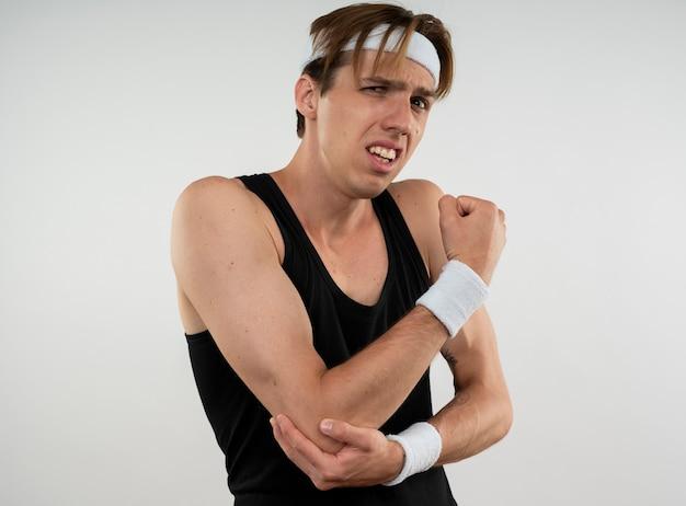Ranny młody sportowy facet w opasce i opasce złapał bolący łokieć na białym tle na białej ścianie