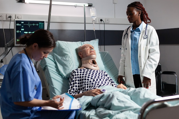 Ranny starszy mężczyzna z ortezą szyi leżący w łóżku, cierpiący po wypadku, rozmawiający z lekarzem podczas wizyty lekarskiej i asystent robiący notatki w schowku