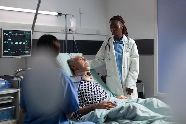 Ranny starszy mężczyzna z ortezą szyi leżący w łóżku