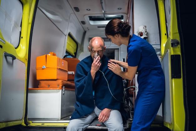 Ranny, zszokowany mężczyzna siedzący z maską tlenową w karetce, opiekuje się nim pracownik medyczny.