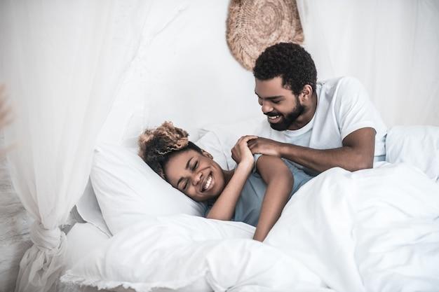 Rano budzę się. przebudzony, młody dorosły człowiek afroamerykanin, dotykając ramienia uśmiechniętej żony leżącej na boku
