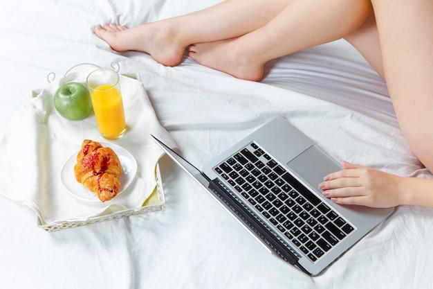 Rano i śniadanie młodej pięknej dziewczyny w łóżku w domu z laptopem. zbliżenie nóg dziewczyny