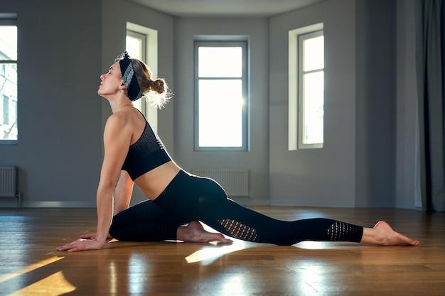 Rano joga dziewczyna robi ćwiczenia rozciągające w pokoju dla pilates. piękne światło, zdjęcia lotnicze, zdrowy tryb życia, hormony ciała i dusza, oświetlenie