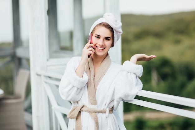 Rano na tarasie hotelu w górach. kobieta rozmawia przez telefon i ma ładną buzię.
