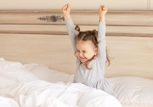 Rano przebudzenie małej dziewczynki w łóżku