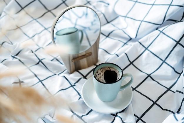Rano przytulny nastrój. kawa w łóżku. filiżanka czarnej kawy w łóżku na białym kocu w kratkę. selektywne skupienie