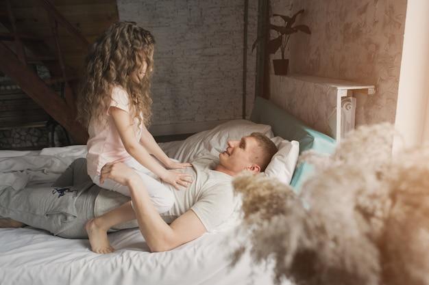 Rano rodzina dzieci z tatą bawiące się w łóżku budząc się ze snu właśnie obudziłem miłość