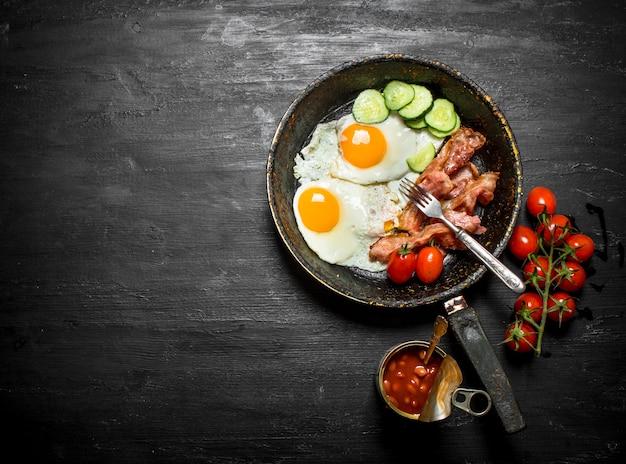 Rano śniadanie na patelni z widelcem. jajka sadzone z boczkiem, fasolą i ogórkami. na czarnym tle drewnianych.