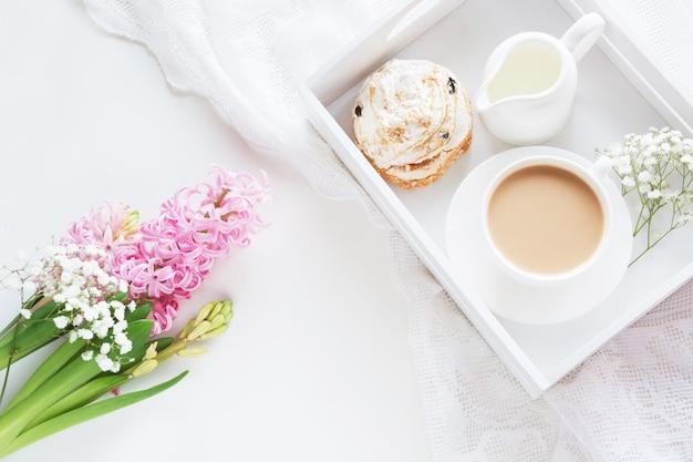 Rano śniadanie na wiosnę z filiżanką czarnej kawy z mlekiem i ciastkami w pastelowych kolorach