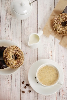 Rano śniadanie z czekoladowymi pączkami i filiżanką kawy ze śmietaną. pyszne pączki posypane kruszonymi orzechami. widok z góry
